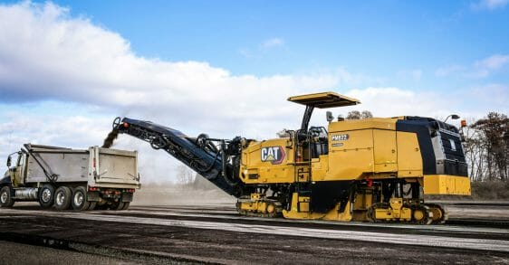Large Cat machine dumping a load into the back of a dump truck