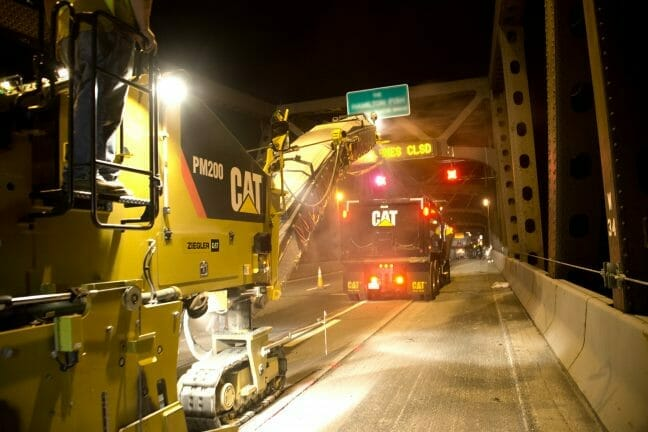 two cat machine driving across a bridge at night.
