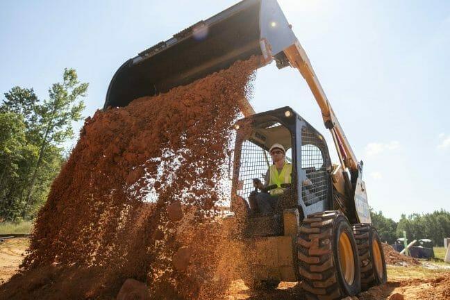 cat skid steer loader dumping mud