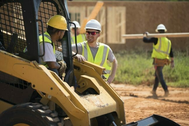two construction workers talking to each other while working with a cat skid steer loader