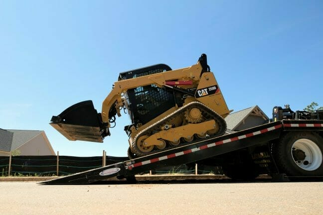 Cat compact track loader on a trailer ramp