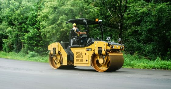 Man in a hard hat driving a Cat Compactor down the road