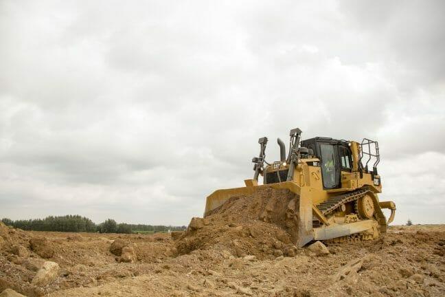 cat machine shoveling dirt in an open field.