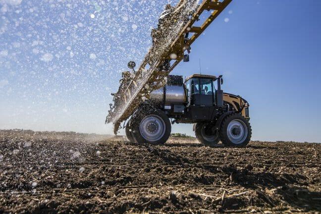 Farming equipment applying liquid to planted crops