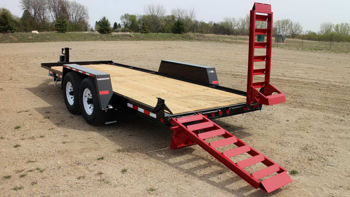 towmaster trailer in a gravel lot with one of the ramps lifted up