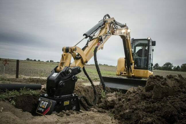 a cat machine digging a hole in a field.