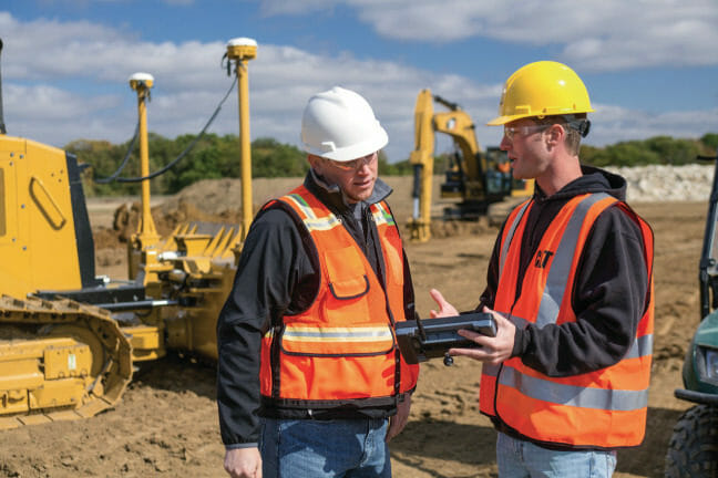 Two men on a construction site, looking at technology device