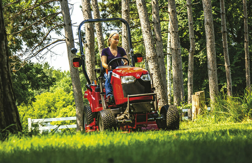 woman riding a red massy ferguson sub compact tractor in the yard