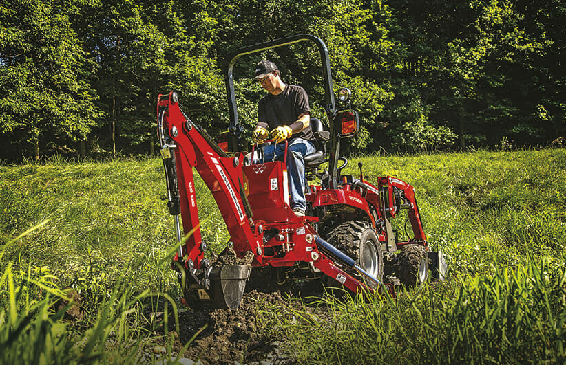 man riding a red massy ferguson sub compact tractor in a field