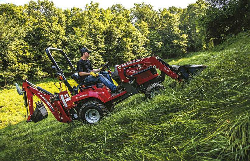 a man riding a red massy ferguson sub compact tractor up a grass hill
