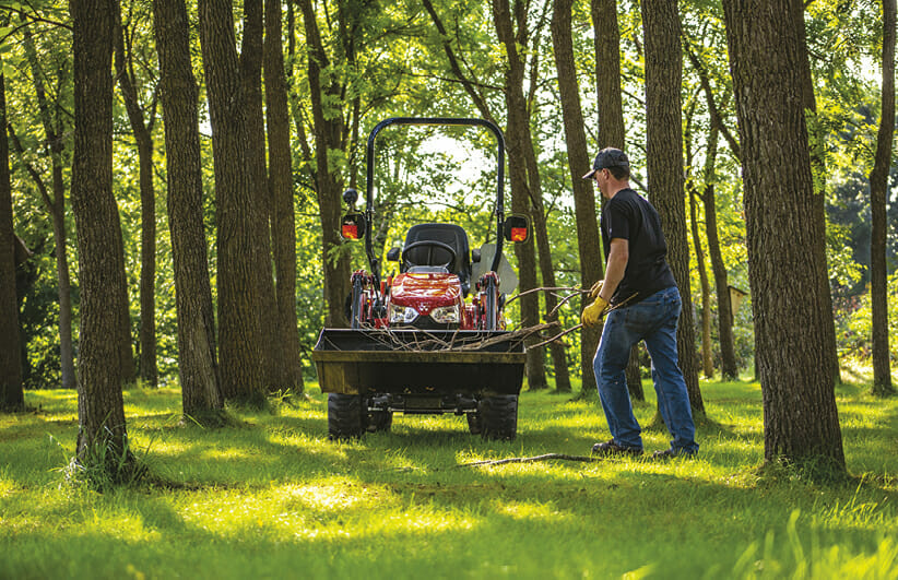 a man picking up sticks in the yard with a red massy ferguson sub compact tractor in the background