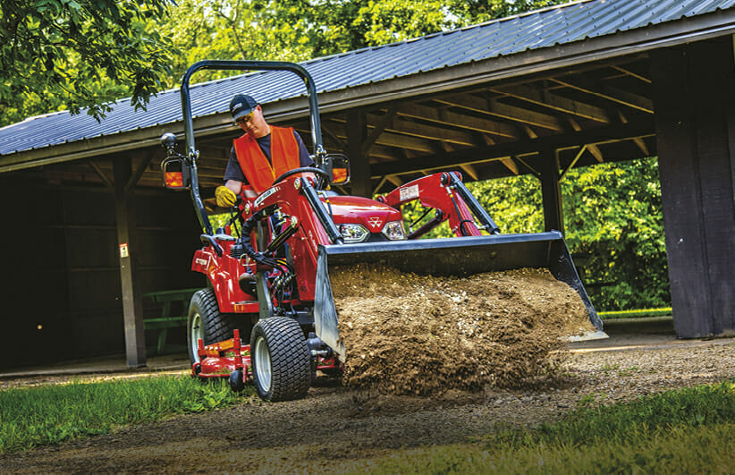 worker using a red massy ferguson sub compact tractor to dump dirt onto the ground