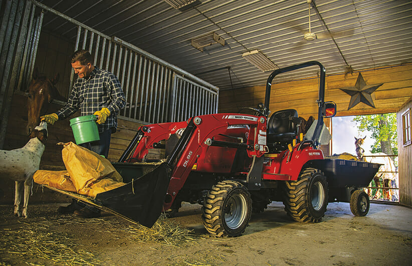 man feeding a dog in the barn with a massy ferguson tractor holding the dog food bags
