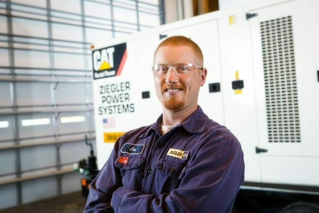 A CAT technician with crossed arms and a smile on his face, standing in front of a CAT power generator